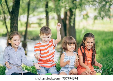 Group Of Smiling Children Relaxing In Park