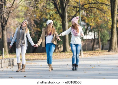 Group of smiling college girls walking in the park - friendship