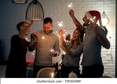 Group of smiling friend having fun with sparkles at home for Christmas in the night.