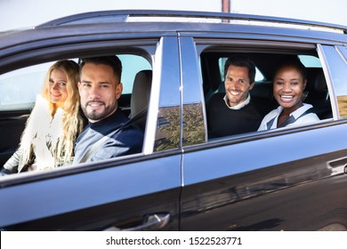 Group Of Smiling Friends In Car On Road Trip Together Looking Out From Window