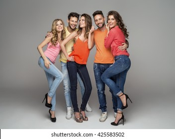Group of smiling friends in fashionable clothes