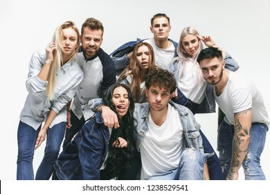 Group of smiling friends in fashionable jeans. The young men and woman posing at studio. The fashion, people, happy, lifestyle, clothes concept