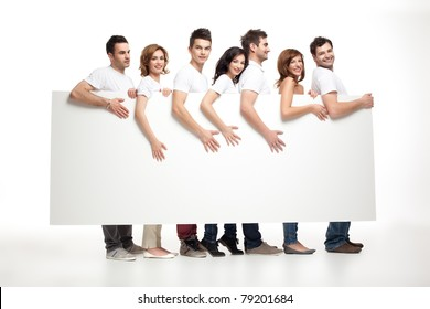 group of smiling friends holding white banner