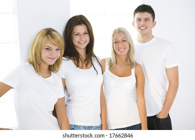 Group of smiling friends standing beside window and looking at camera. They have on white t-shirt. Front view.