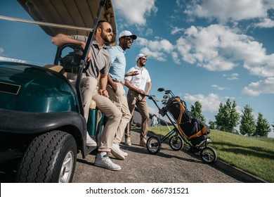 group of smiling friends standing near golf cart and looking away