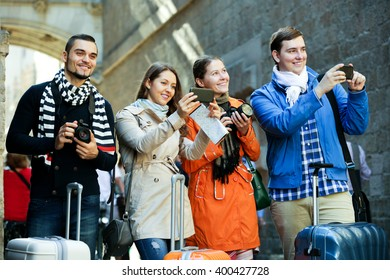 Group of smiling friends walking through street with camera and smartphone