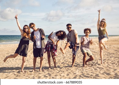 group of smiling friends wearing summer clothes and sunglasses jumping on beach
