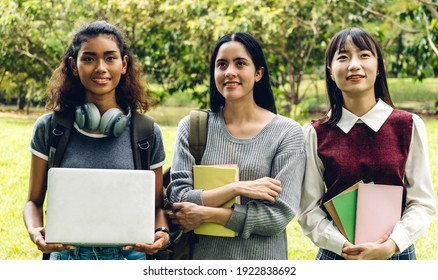 Group of smiling international student or teenagers standing with book in park at university.Education and friendship Concept