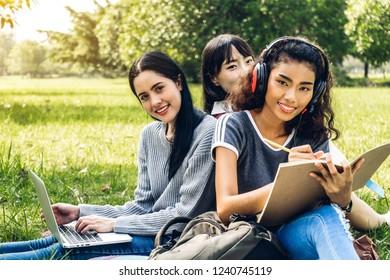 Group of smiling international students or teenagers sitting and using laptop computer doing their homework with book together in park at university.Education and friendship Concept