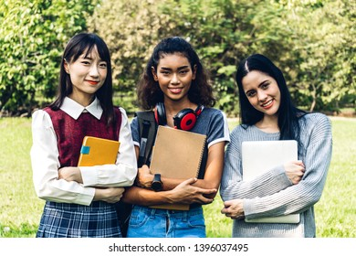 Group of smiling international students or teenagers standing and hugging together in park at university.Education and friendship Concept