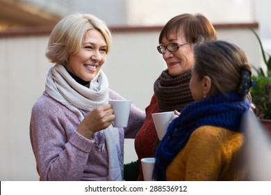 Group of smiling mature women drinking tea at balcony