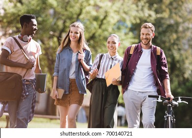 group of smiling multicultural students spending time together in park