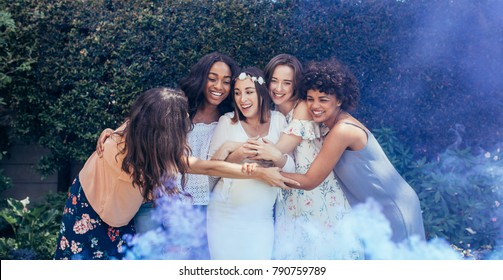 Group of smiling multi-ethnic female friends hugging pregnant woman outdoors. Expecting mother and her friends with smoke grenade at baby shower.