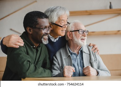 group of smiling multiethnic senior friends embracing and looking away