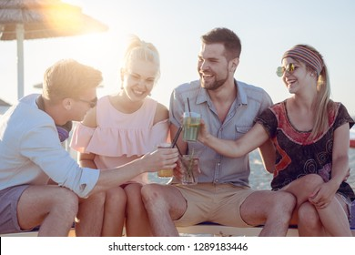 group of smiling people drinking cocktails on sunny day on a beach vacation. 4 young friends cheers with drinks sitting on beach. concept of friendship togetherness and joy