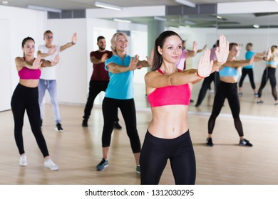 Group of smiling people training sport dance in fitness studio