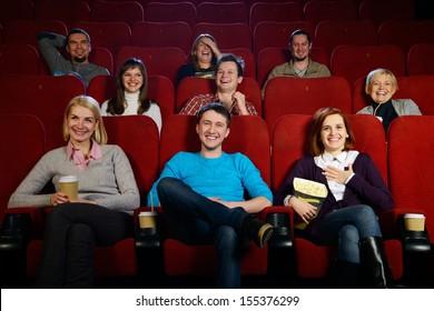 Group of smiling people watching movie in cinema