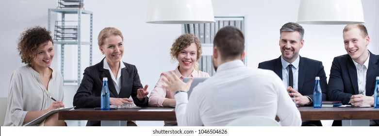 Group of smiling recruiters listening to a man with good references