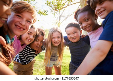 Group of smiling schoolchildren lean in to camera embracing