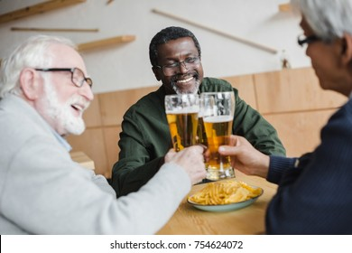 group of smiling senior friends clinking glasses of beer in bar
