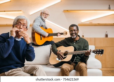 group of smiling senior friends playing music with guitars and harmonica