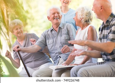 Group of smiling senior friends spending time together sitting in the park