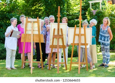 Group of smiling senior women painting on canvas during sunny day in garden.