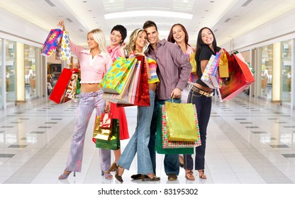 Group of smiling shopping people in modern mall.