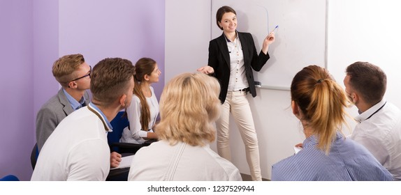 Group of smiling students attentively listening to lecture of female teacher in classroom