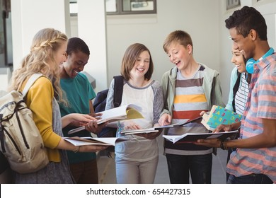 Group of smiling students standing with notebook in corridor at school