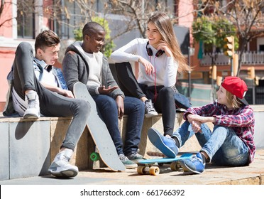 Group of  smiling teenage friends relaxing and chatting in town square
