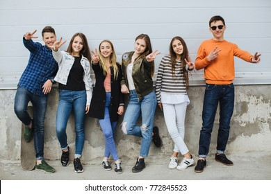 Group of smiling teenagers with skateboard hanging out outside.