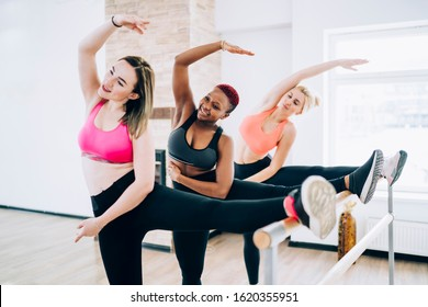 Group of smiling toned multiethnic sportswomen standing with one leg on barre and reaching over leg with opposite arm in bright fitness room
