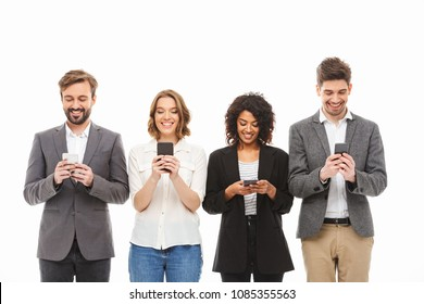 Group of smiling young business people using mobile phones isolated over white background