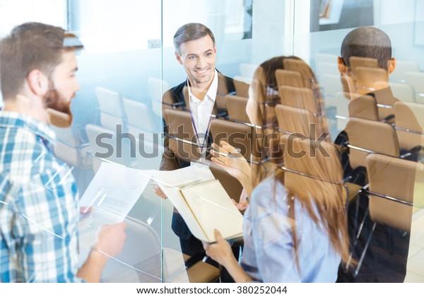 Gruppe lächelnder junger Geschäftsleute, die im Konferenzsaal stehen und neue Ideen diskutieren