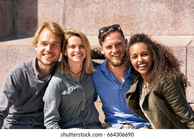 Group of smiling young multiracial friends sitting close to each other as a friendship and togetherness concept
