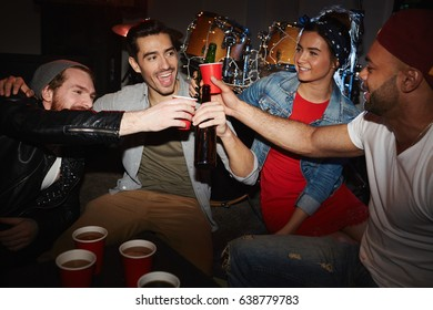 Group of smiling young party people drinking beer and raising glasses hanging out in night club on stage