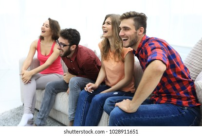 group of smiling young people sitting on the couch