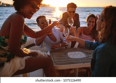 Group of smiling young people toasting at boat party during sunset. Men and women enjoying at a boat party.