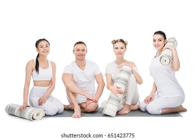Group of smiling young women with trainer sitting together with yoga mats isolated on white