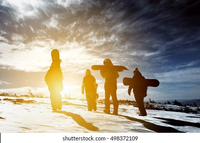 Group snowboarders goes to sunset. Snowboarding concept