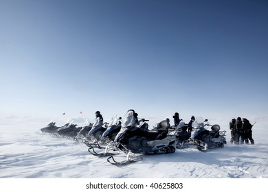 A group of snowmobiles travelling accross a barren winter landscape