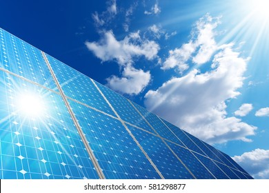 Group of solar panels on a blue sky with clouds and sun rays - Concept of solar energy