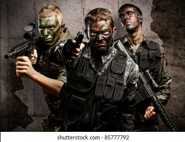 group of soldiers aiming with rifles against a grunge bricks wall