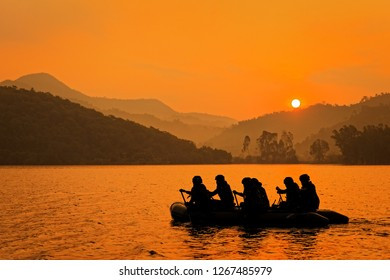 Group of soldiers help to row boat to target at twilight, mountain and sun in background.
