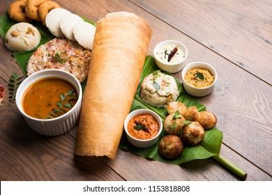 Group of South Indian food like Masala Dosa, Uttapam, Idli/idly, Wada/vada, sambar, appam, semolina halwa, upma served over banana leaf with colourful chutneys, selective focus