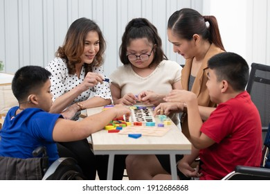 Group of special students in classroom, a down syndrome girl, two handicapped boys and cute Asian teacher playing toy and game together.