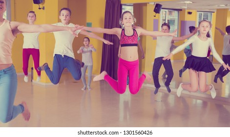 Group of sportive children with female teacher training in modern dance hall, jumping together