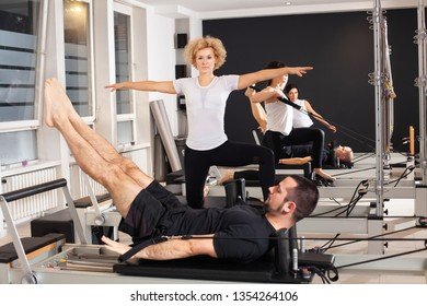 Group of sporty and athletic people are working out Pilates exercises with instructor on special equipment in modern studio interior. Fitness, sport, training and people concept
