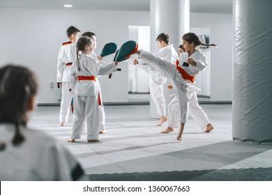Group of sporty Caucasian children in doboks having taekwondo class in white gym.